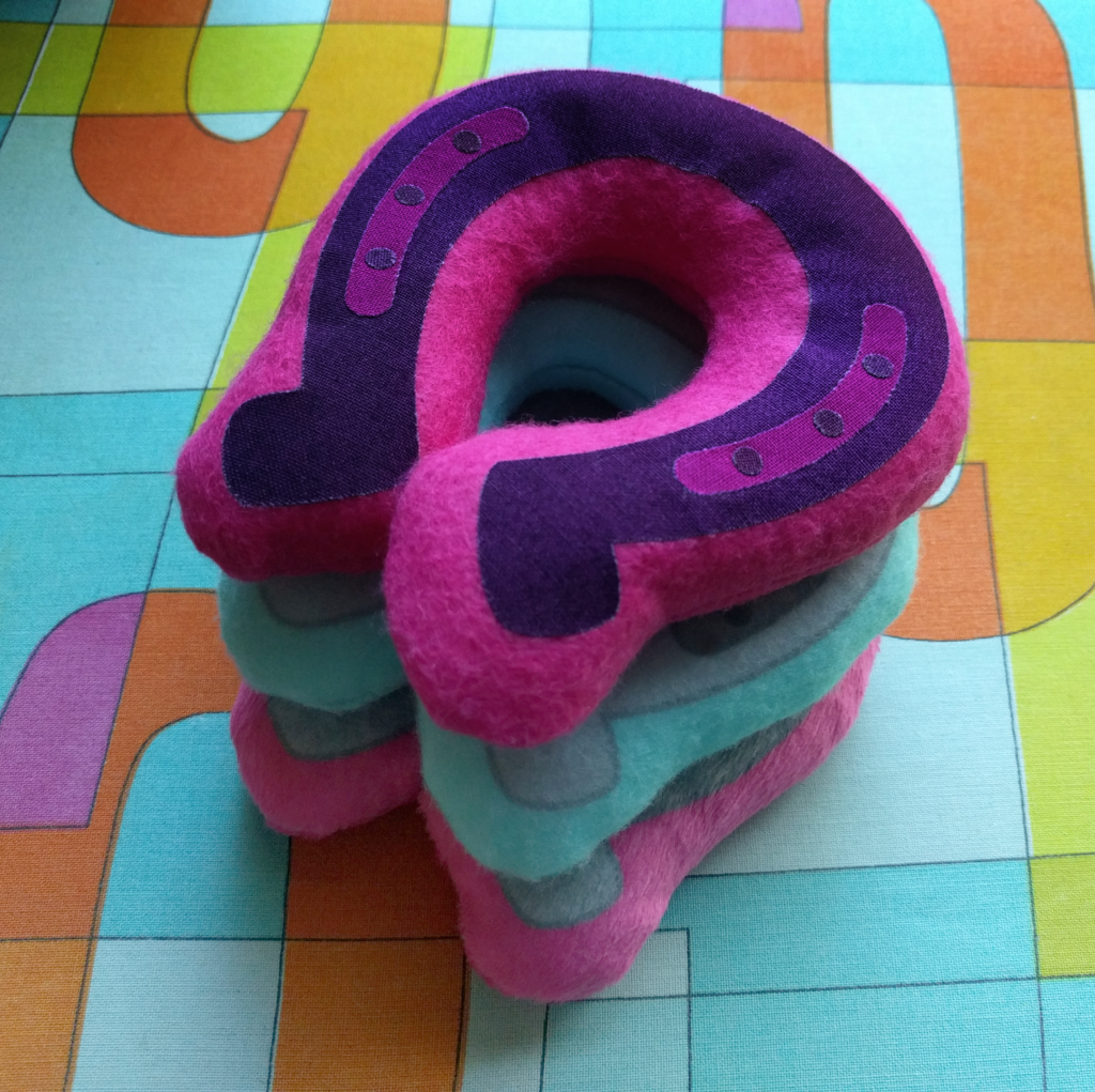 3 colorful bean bags shaped like horseshoes stacked on top of each other